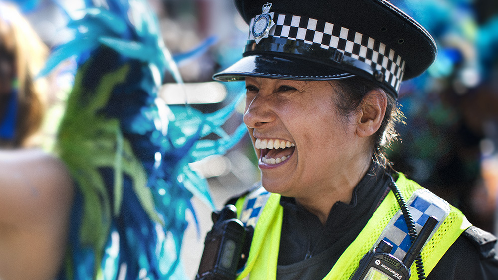 Image of female police officer laughing with carnival go-er.
