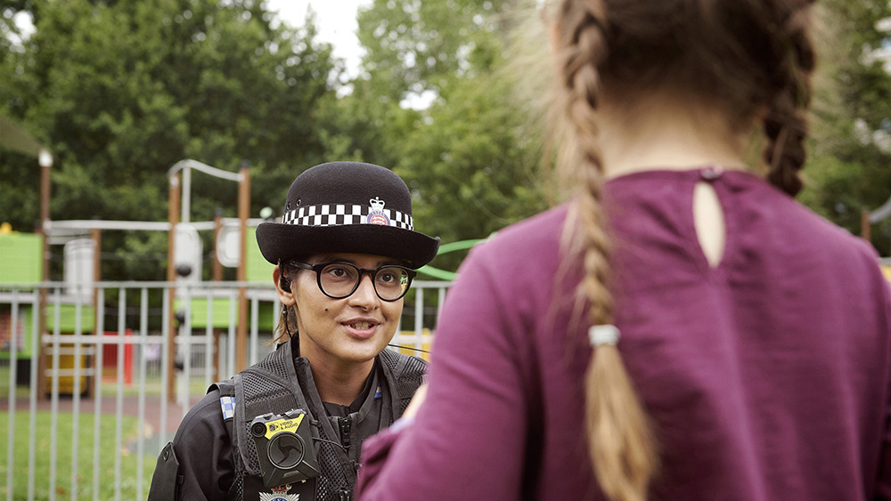 Female police officer talking to child.