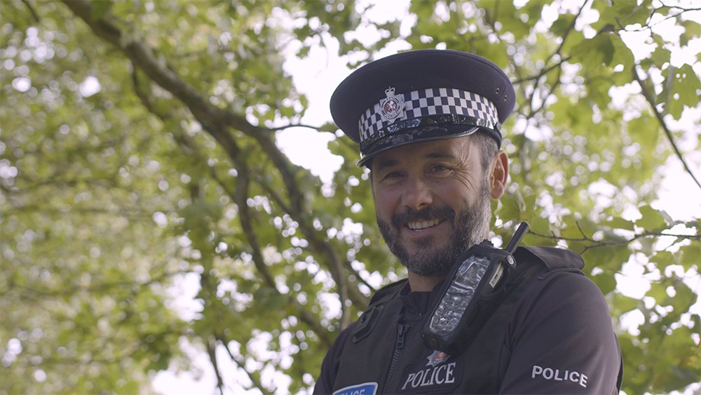 Image of male police officer smiling.