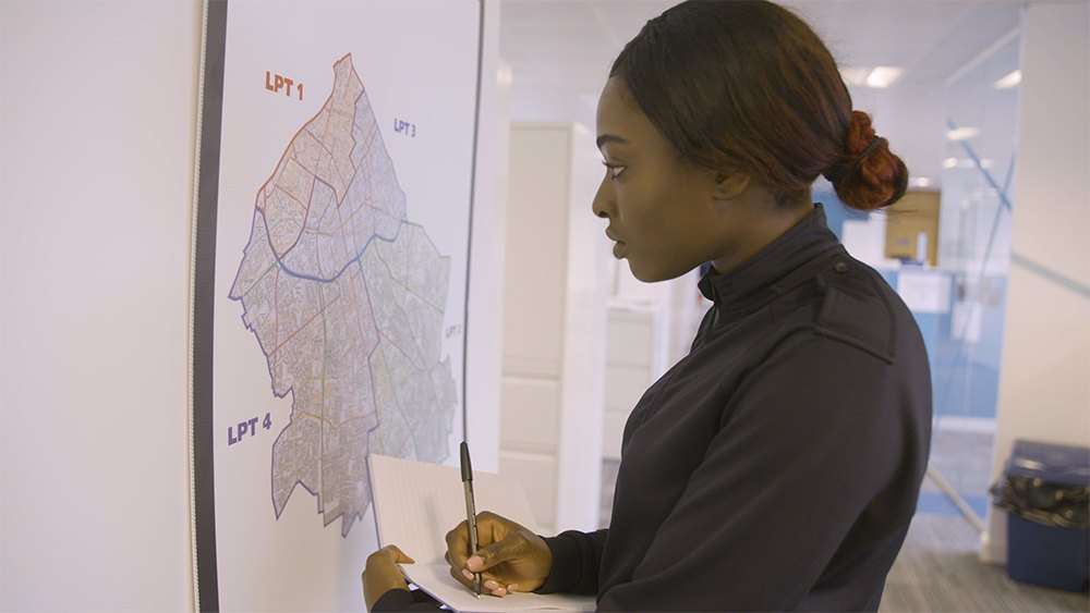 Image of female police officer taking notes from map