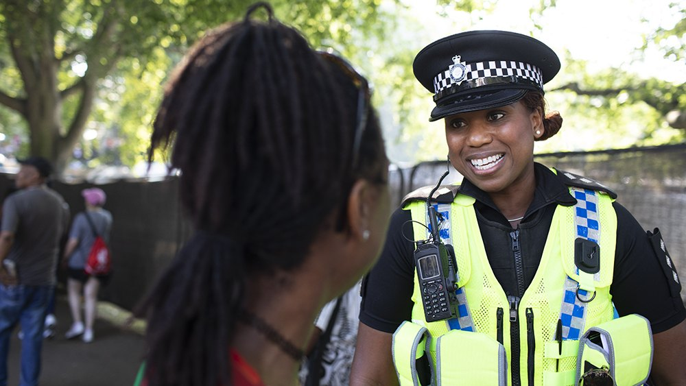 Image of female police officer talking to member of the public.