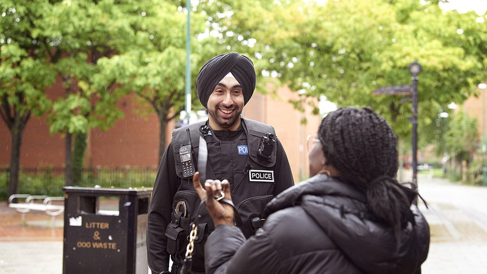 Male officer talking to member of the public.