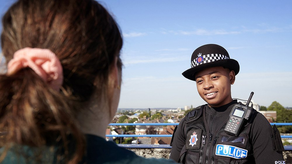 Female officer smiling with cityscape in background.